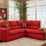 Red sectional with chaise and decorative pillows grey area rug round glass top side table with metal base battery powered table lamp