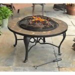 Round Hampton bay fire pit table idea with black metal legs