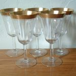 Set-of-5-Vintage-Tiffin-Minton-Gold-Encrusted-Optic-Etched-Gold-Rim-Wine-Glasses-Crystal-with-etched-gold-encrusted-rim-and-a-paneled-bowl-placed-on-wooden-table