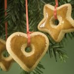 Gingerbread ornaments on fir branch isolated against green paper