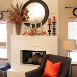 White Rustic Mantel Decor Of Fireplace With Round Mirror And Grey Chair