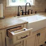 White farm kitchen sink and black wrought iron faucets white painted wooden base kitchen cabinet units