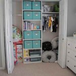 White finished wood closet organizer design with several blue box storage units