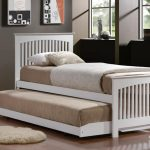 White painted wood trundle bed with additional bed and mall white shag rug in bedroom