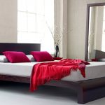 Wooden Low Profile Platform Bed Frame With White Mattress Red Pillows And Sheet Near Long Mirror