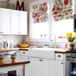 adorable and colorful kitchen design with white cabinetry and floral patterned curtain with red and white runner rug