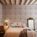 adorable bedroom design with playful wallpaper accent and wooden ceiling decoration and floor mirror and tufted chair