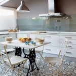 adorable black and white patterned tile flooring in the kicthen beneath white wooden dining table with white vinatage chairs and white cabinetry