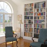 adorable classic interior design with large built in bookshelves design and navy blue chairs and wooden floor and arched window and floor lamp