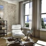 adorable corner interior of apartment with white leather luxurious reclining chair and wooden floor and cow patterned area rug