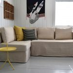 adorable creamy  slip cover for sectional design with orange and black cushions and round yellow end table and wall pictures