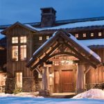 adorable entrance shape of wooden house dsign wih vaulted canopy and log pole and wooden barn door and siding
