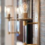 adorable vintage wall lamp design with copper holder and golden tone with transparent shade and bulb on wooden siding