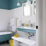adorable white and blue bathroom color trend idea with soft blue bathtub and floating vanity with white bench and wall lamps