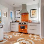 adorable white kitchen design with orange accent and wall pictures and beige wooden flooring with pattern