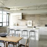 adorable white kitchen loft design with wooden backsplash and white island with gray concrete flooring and wooden dining table and glass window