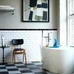 adorable white loft bathroom design with brick wall accent with white modern bathtub and vintage black leather chair and glass window and plaid floor
