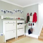 adorable white shoe storage in the entry esign with floating racks and pictures on the wall and clothes hook