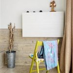 adorable yellow chair design in apartment interior with white foldable desk and blue throw and wooden wainscotting and floor and indoor plant