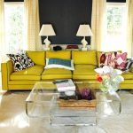 adorable yellow couch design with colorful cushions and acrylic coffee table and white table lamps and creamy curtain