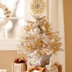 Beautiful White Tabletop Christmas Tree In The Pot Placed Near Gifts With Star Ornaments And Other White And Gold Ornaments