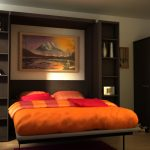 bedroom design idea with murphy bed kit lowed and orange bedding with pink pillows and brown floor
