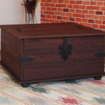 best classic and antique wooden coffee table furniture design in boxy shape with lock on ethnic patterned area rug with reddish brick wall accent