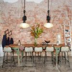 best loft kitchen design idea with red brick wall accent and wooden dining table with white stools and industrial pendants and concrete flooring