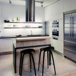 best loft kitchen interior design with wooden small island with black stools and lamp track and white cabinetry