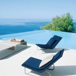 best luxurious house with infinity swimming pool overlooking ocean with stunning white patio deck with navy blue pool chairs