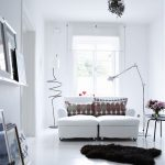 best scandinavian interior with two sections sofa and patterned cushions and black area rug and floor lamp and glass window and pendant