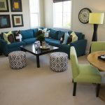 blue apartment sectional sofa with gorgeous coffee table and round patterned ottoman plus dining space and ivory area rug
