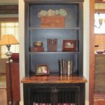 bookshelf-dog-crates-with-cabinets-dog-kennel-and-shelves-in-black-and-wooden-material-with-books-photos-and-decorative-items-above-the-crate