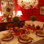 cheerful red christmas centerpiece design on dining table with topiary and red ribbon and crystal chandelier and vanity