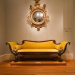 classic and luxurious yellow couch idea with brown wooden frame with wing back and staged style beneath antique wall mirror