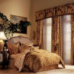 classic bedroom design with bold luxurious bedding and purple headboard and white sheer curtain and indoor plant