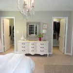 classic master bedroom design with walk in closet and white vintage vanity with wall mirror and creamy flooring and white bedding and chandelier
