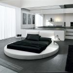 classy black and white round bed idea with large bedroom and open plan and gray flooring and white cabinetry and black area rug