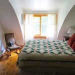 comfortable bedroom of beaverbrook quonset hut homes featuring comfortable bed and rocking chair and wooden floor