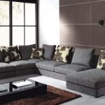 Comfortable Living Room Design With Tile Wall Design And Glass Window With Black Frame And Gray Sofa With Patterned Cushion And Black Coffee Table