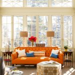 comfortable orange chesterfield sofa design with hexagonal patterned coffee table and lamps and chandelier and glass window