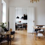 comfortable white scandinavian interior decor with black wire chairs and esk with large bookshelves and wooden floor