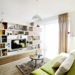 creative apartment design with green sofa design and gray area rug and bookshelves partition and large glass window and wooden floor and brown curtain