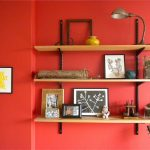 diy wooden wall shelves design on red painted wall with black iron stand and table lamp with glass window