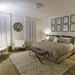 elegant apartment bedroom design with creamy bedding and white sofa with tufted patterna  and wooden floor and patterned rug