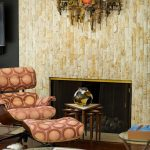 elegant interior design with antique wall feature and fireplace and soft patterned ergonomic reclining chair