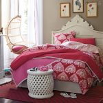 elegant pink bedroom design with carved headboard and round bench and comfy chair for bedroom design on red carpet