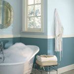 elegant soft blue bathroom color trend with freestanding white bathtub and black iron table with glass window and round wall mirror