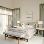 elegant white creamy bedroom design with sheer curtain idea and bench and white area rug and creamy end tables