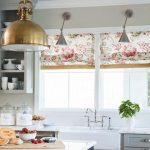 elegant white kitchen design with floral patterned curtain on glass window with indoor plant and black white island with golden vault
